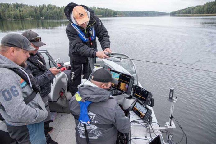 Perttu Haanpää selostaa kalastustekniikkaa Toni Pohjalaisen ajaessa venettä. Erä-lehden Teemu Koski ja Kalastajan Kanavan Jyri Kuusisalo omaksuvat tietoa.